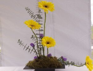 The bright pop of yellow sunflowers with a touch of purple show subtle beauty.